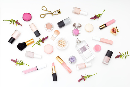 Set of cosmetics on a white background and twigs of flowers. Flat lay