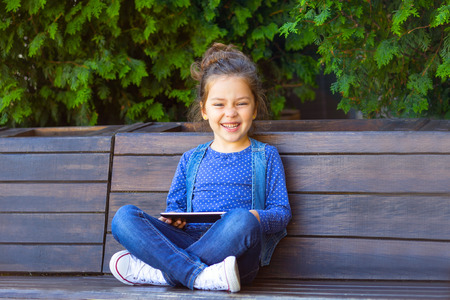 Little girl  play in tablet outdoors and smiling. Working Outside with Technology