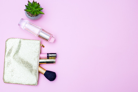 Shiny golden cosmetic bag and perfume on a pink background. Copy space