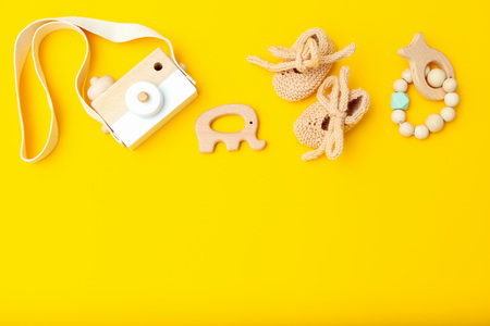 Wooden toys and baby shoes on a yellow background. Copy space