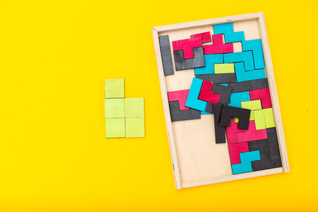 Wooden multicolored puzzle on yellow background. Flat lay Banque d'images - 118784784