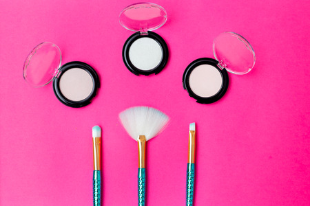 Makeup brushes mermaid tail  and eye shadow on a bright pink background. Flat lay