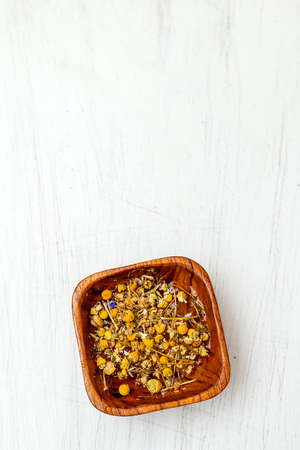 Dry chamomile flowers in a wooden bowl. Copy space