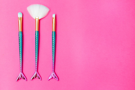 Mermaid makeup brush on bright pink background. Copy space