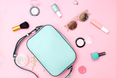 Female accessories and make up pastel color on pink background. Flat lay Imagens