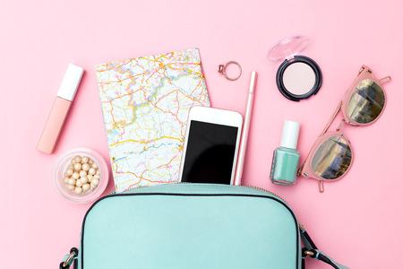 Accesorios para viajar sobre fondo rosa. Endecha plana Foto de archivo