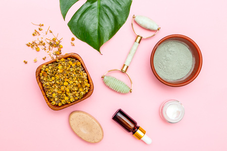 Natural skin care and face roller on pink background. Flat lay