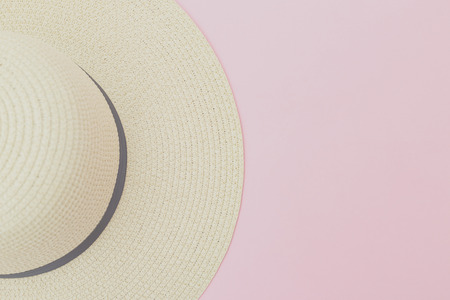 Straw hat on pink background. Travel vacation concept.