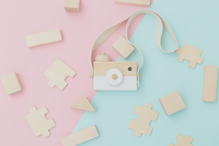 Wooden  toy camera on pastel color background. Flat lay Banco de Imagens