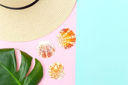 Straw hat and seashells on pastels color background. Copy space
