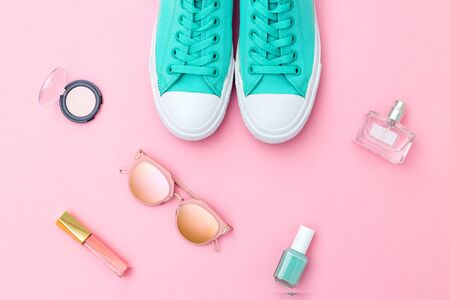 Shoes and and make up on  pink background. Flat lay