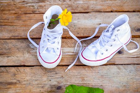 White sneakers with a yellow flower on a wooden background. Flat lay