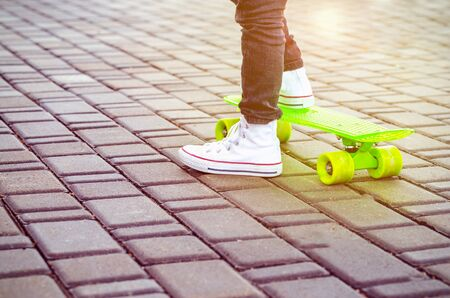 Green skateboard and kids sneakers. Outdoors