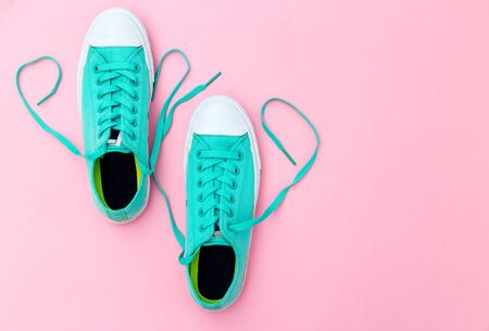 Green sneakers on pink background. Lifestyle look