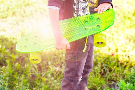 Boy skater holds in his hand a neon green skateboard. Outdoors Banco de Imagens