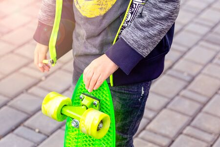 The boy holds in his hand a green skateboard. Childhood