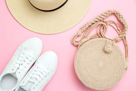 Wicker hat and handbag for the beach on pink background. Flat lay