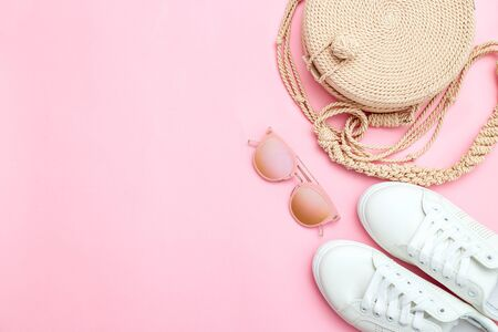 Trendy feminine accessories on pink background. Copy space