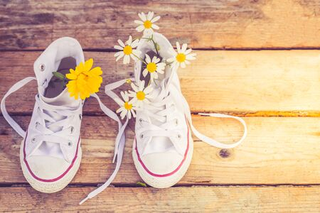 White trendy sneakers and flowers on wooden background. Copy space