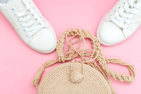 White trendy sneakers  and wicker bag on pink pastel background. Front view. Minimal concept.