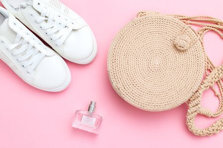 Womens wicker handbag and white sneakers with a perfume on a pink background. Flat lay Banco de Imagens