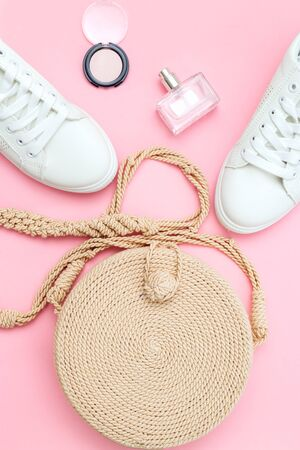 White trendy sneakers  and feminine accessories on pink pastel background. Front view. Vertical