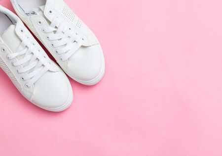 Toes of white trendy sneakers on pink background. Place for text. Banco de Imagens