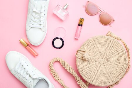 White trendy sneakers and feminine accessories  on pink background. Flat lay