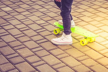 White sneakers and green neon skateboard. Copy space Stock Photo