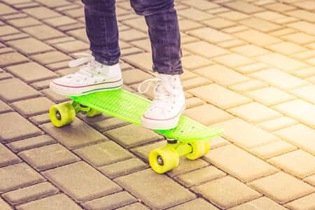 White sneakers and green neon skateboard. Childhood