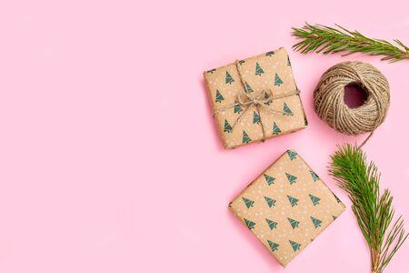 Christmas gift box and sprigs of Christmas tree on pink background. Hand made
