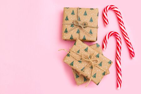 Christmas gift box and Christmas candy cane on pink background. Copy space