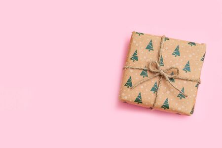 Christmas gift on pink background. Copy space