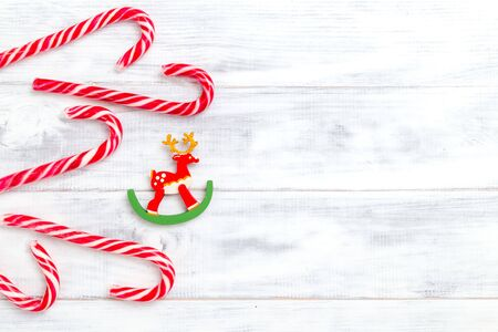 Christmas candy cane and deer on wooden background. Copy space