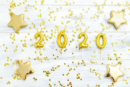 Happy New Year 2020. Symbol from golden number 2020 and golden sparkle on white wooden background.