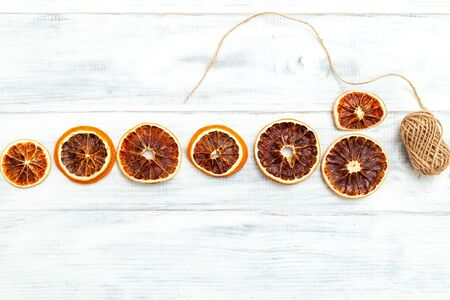Dried Orange Slices For Christmas Orange Slice Garland on white wooden background. Flat lay