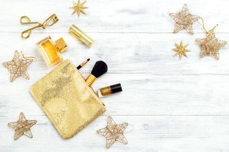 New year, holiday makeup in gold tones on a white wooden background. Copy space Imagens