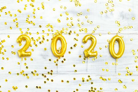 Happy New Year 2020 gold numbers on white wooden background and golden sparkle. Flat lay