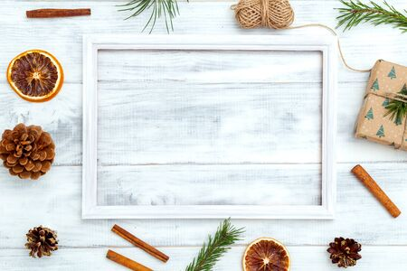 Christmas composition. White wooden frame on white wooden background. Copy space