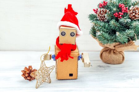 Cardboard robot with hands in santa hat on a white wooden background and christmas tree. Christmas composition 写真素材