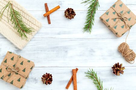 Christmas composition. Christmas gift, knitted blanket, pine cones on white wooden background