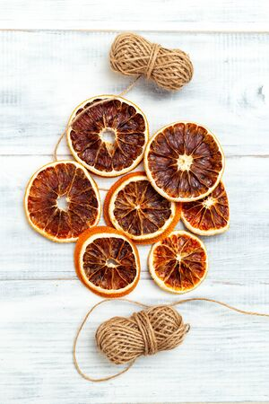 Dried Orange Slices For Christmas Orange Slice Garland on white wooden background. Vertical
