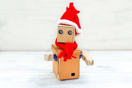 Cardboard robot with hands in santa hat on a white wooden background. Christmas composition