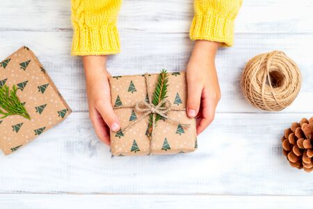 Hands in a yellow knitted sweater hold a box for Christmas. Flat lay