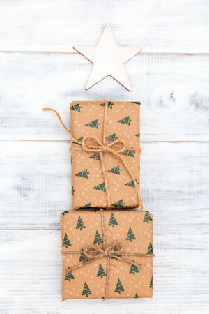Gift box  for christmas craft paper on white wooden background. Vertical
