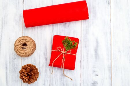 Christmas Red gift box with  fir branches and Christmas decorations  on white wooden background. Copy space