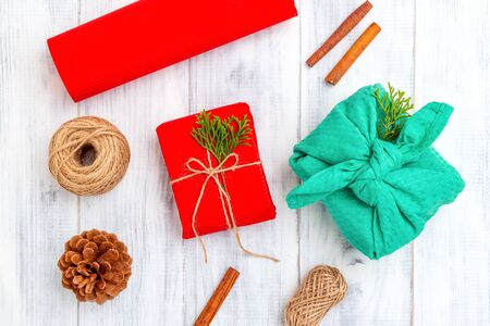 Furoshiki and Christmas gift red box on white wooden background. Hand made 写真素材