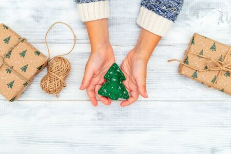 Christmas tree made of felt in hands  with gift on a white wooden background. Flat lay