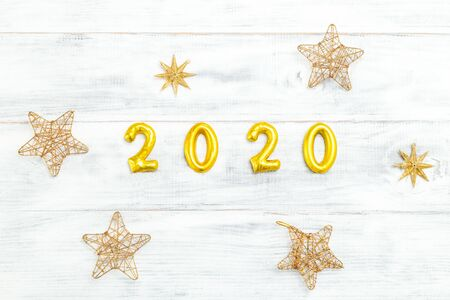 2020 New Year shiny golden color and stars on white wooden background. Flat lay 写真素材