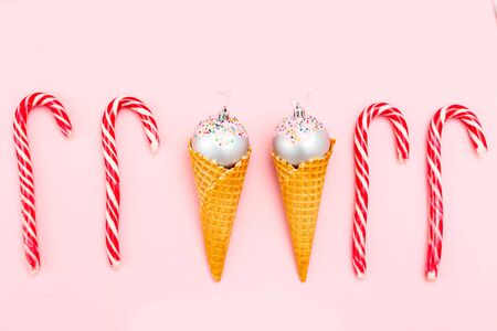 Christmas ball sweet in waffle cone and Christmas candy caneon pink background.  Flat lay